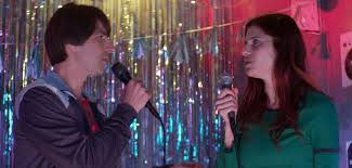 Carol (Bell) and Louis (Martin) having a good time with karaoke