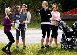 Noelle (Casey Wilson) and Amy (Rosamund Pike) . . . Amy singular as childless among the mothers