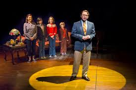 Michael Cerveris as Bruce, with the Bechdel family arranged behind him